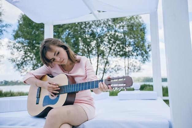 Dziewczyna Z Krzywym Głowy Podczas Gry Na Gitarze Darmowe Zdjęcia