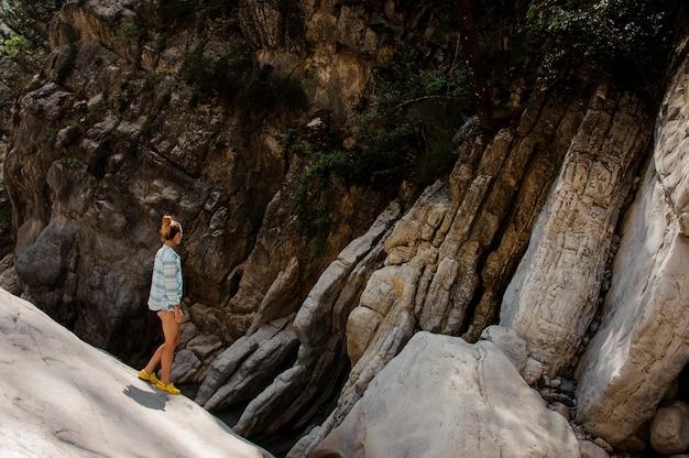 Dziewczyna z kucykiem chodzi na kamieniach w jarze Premium Zdjęcia