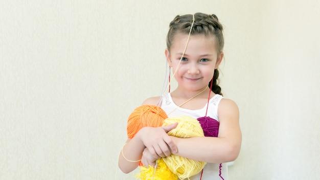Dziewczyna z kulkami nici do dziania. Premium Zdjęcia