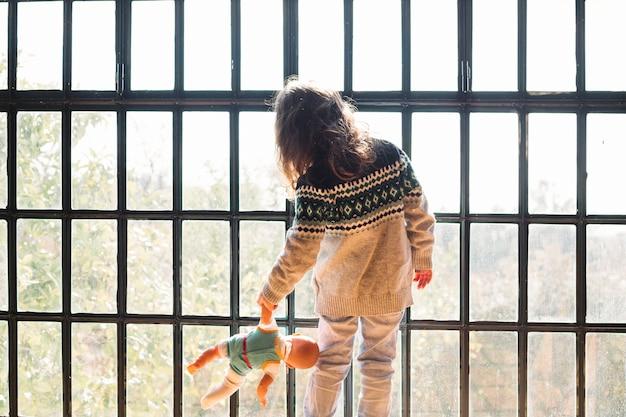 Dziewczyna Z Lalką Patrząc Przez Okno Darmowe Zdjęcia