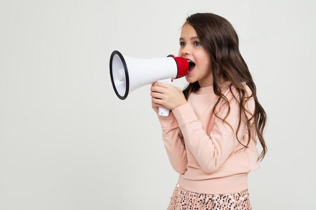 Dziewczyna Z Megafonem W Ręku Na Boki Na Białej ścianie Studio Z Pustą Przestrzenią Premium Zdjęcia