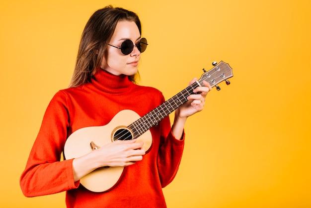 Dziewczyna z okularami przeciwsłonecznymi bawić się ukelele Darmowe Zdjęcia