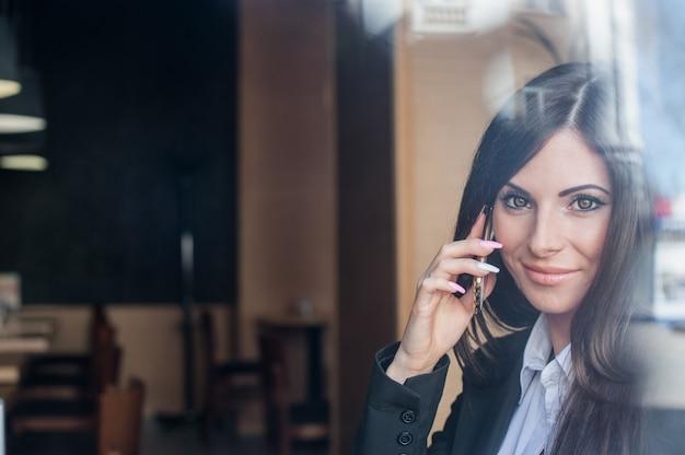 Dziewczyna z pięknymi oczami rozmawia przez telefon Premium Zdjęcia