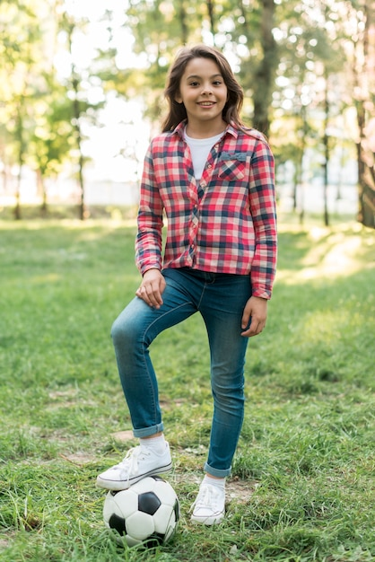 Dziewczyna z piłki nożnej pozycją na trawie przy parkiem Darmowe Zdjęcia