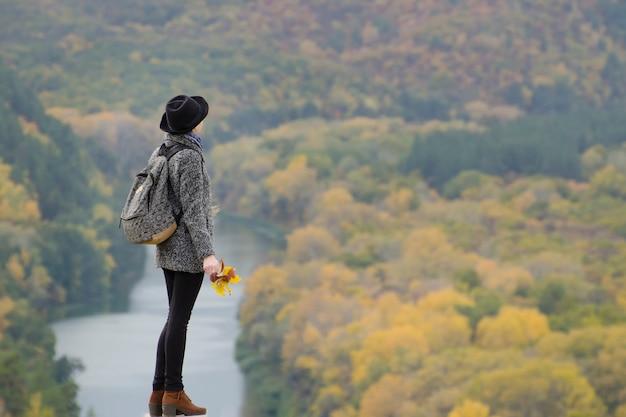 Dziewczyna z plecakiem i kapeluszową pozycją na wzgórzu Premium Zdjęcia