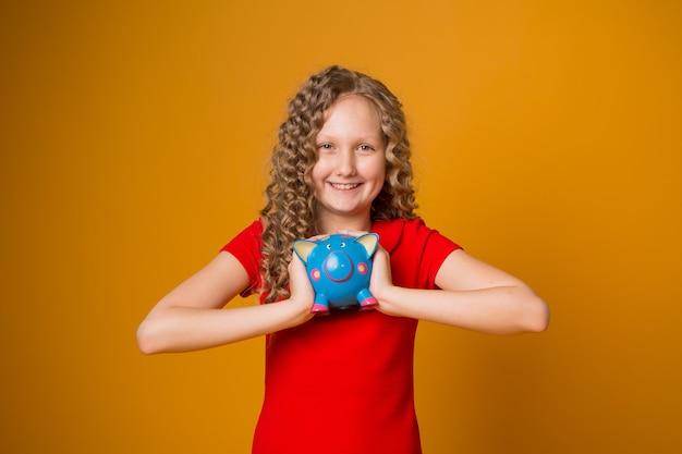 Dziewczyna z prosiątko bankiem w ona ręki Premium Zdjęcia