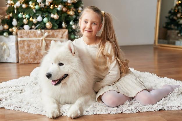 Dziewczyna z psem w pobliżu choinki Premium Zdjęcia