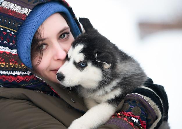 Dziewczyna Z Szczeniaka Husky Na Zimy Tle Premium Zdjęcia