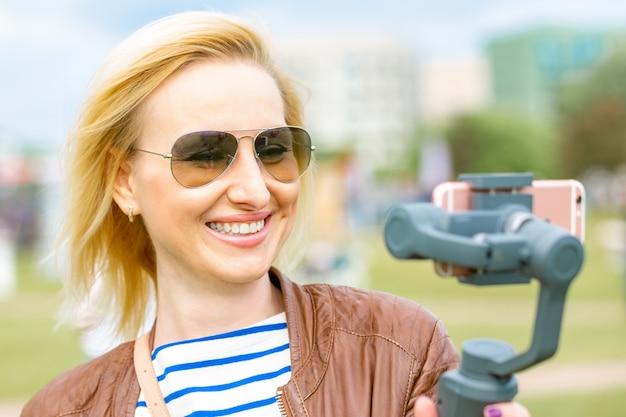Dziewczyna Z Telefonem Na Stabilizatorze Prowadzi Wideoblog. Przenosi Się Do Aparatu Smartphone Premium Zdjęcia