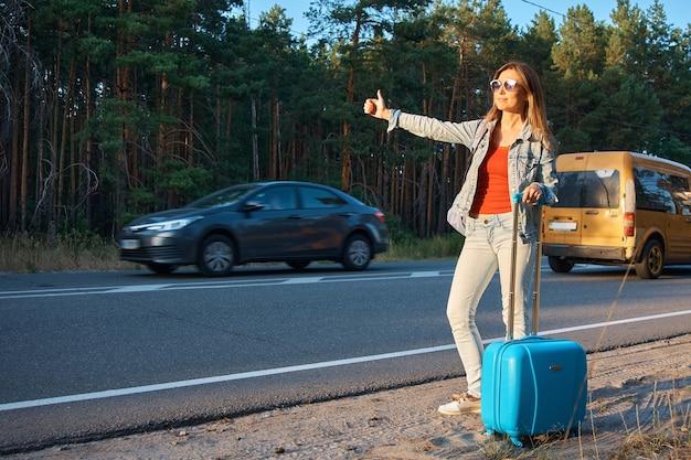 Dziewczyna Z Walizką Jedzie Autostopem. Premium Zdjęcia
