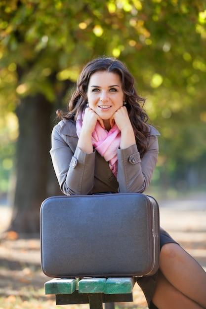 Dziewczyna z walizką przy jesienią plenerową. Premium Zdjęcia