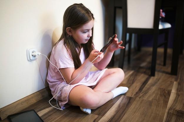 Dziewczyna za pomocą ładowania smartphone Darmowe Zdjęcia
