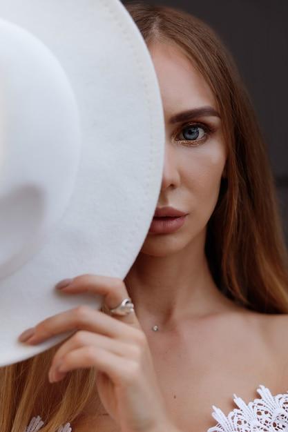 Dziewczyna Zakrywa Twarz Czapką. Połowa Twarzy Premium Zdjęcia