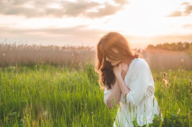Dziewczyna Zamknęła Oczy, Modląc Się Na Polu Podczas Pięknego Zachodu Słońca Premium Zdjęcia