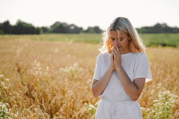 Dziewczyna Zamknęła Oczy, Modląc Się Na Polu. Ręce Złożone W Koncepcji Modlitwy Za Wiarę. Premium Zdjęcia
