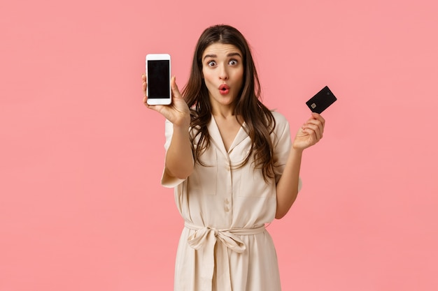 Dziewczyna Zmarnowała Wszystkie Pieniądze Na Konto Bankowe Podczas Imprezy Rabatowej, Trzymając Głupio Składane Usta Karty Kredytowej, Pokazując Ekran Smartfona, Stojąc Zdziwioną Różową ścianą Premium Zdjęcia