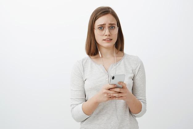 Dziewczyna Zmartwiona Zepsuła Się Jedna Słuchawka. Portret Niezadowolonej I Zmartwionej Zdenerwowanej Uroczej Kobiety W Okularach Z Krótkimi Brązowymi Włosami Marszczy Brwi I Robi Smutną Minę, Trzymając Smartfon W Słuchawkach Darmowe Zdjęcia