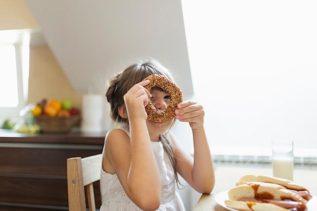 Dziewczynka Bawić Się Z Preclem Z Ziarnami Darmowe Zdjęcia