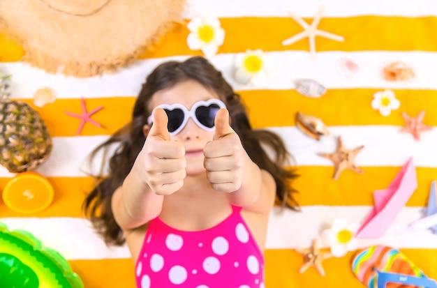 Dziewczynka Dziecka Na Ręczniku Plażowym Nad Morzem. Selektywna Ostrość. Dziecko. Premium Zdjęcia