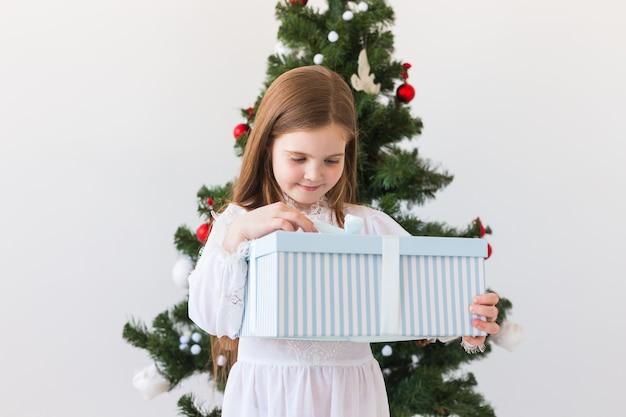 Dziewczynka Dziecko Otwiera Pudełko Obok Choinki Premium Zdjęcia
