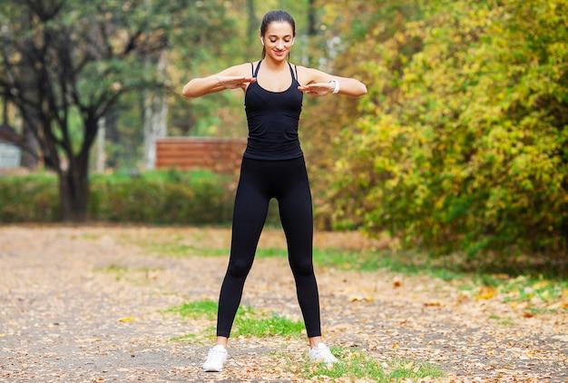 Dziewczynka fitness, młoda kobieta robi ćwiczenia w parku. Premium Zdjęcia