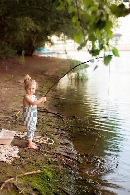 Dziewczynka Na Piaszczystej Plaży W Pobliżu Rzeki Trzyma Wędkę Premium Zdjęcia