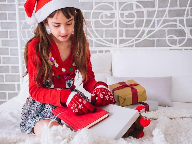 Dziewczynka otrzymała czerwoną książkę jako prezent w boże narodzenie Premium Zdjęcia