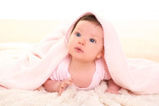 Dziewczynka pod ukrytym różowym kocem na białym futrze Premium Zdjęcia