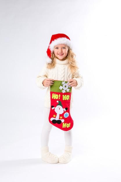 Dziewczynka w czapce mikołaja trzyma skarpetę świąteczną Premium Zdjęcia