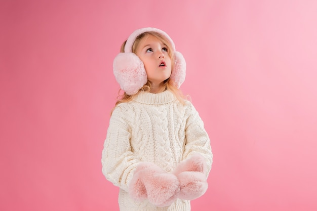Dziewczynka W Różowe Rękawiczki I Słuchawki Na Różowej ścianie Premium Zdjęcia