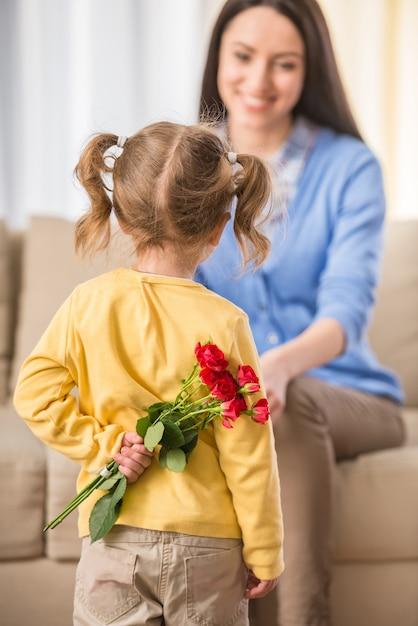 Dziewczynka z bukietem pięknych róż za plecami. Premium Zdjęcia