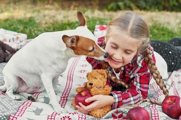 Dziewczynka z psem jackiem russellem terrierem przy choince z prezentami, Premium Zdjęcia