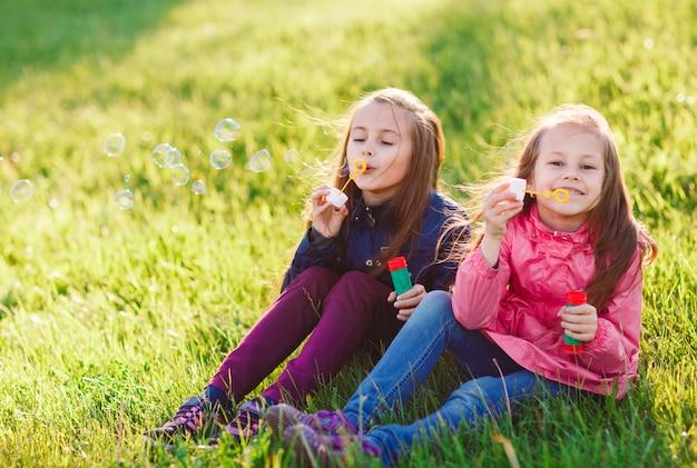 Dziewczyny Bawią Się Bańkami Mydlanymi. Premium Zdjęcia