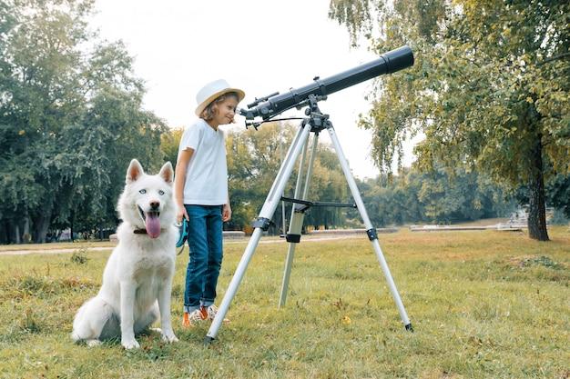 Dziewczyny Dziecko Z Białym Psem Patrzeje Przez Teleskopu Przy Niebem Premium Zdjęcia