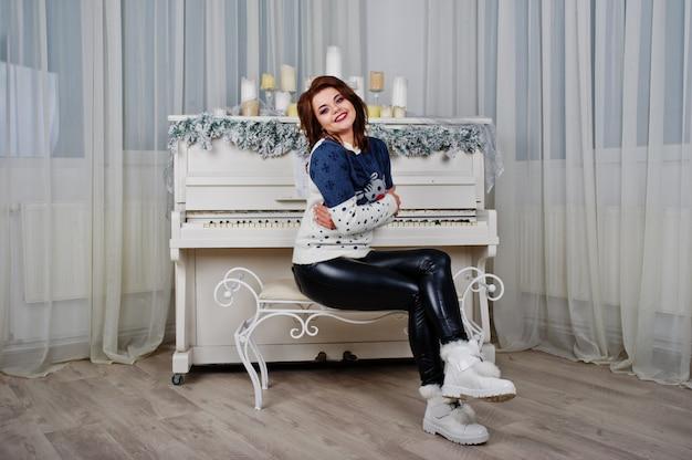 Dziewczyny odzieży puloweru tła ciepły pianino z świeczkami na studiu. szczęśliwego nowego roku ferie zimowe koncepcji. Premium Zdjęcia