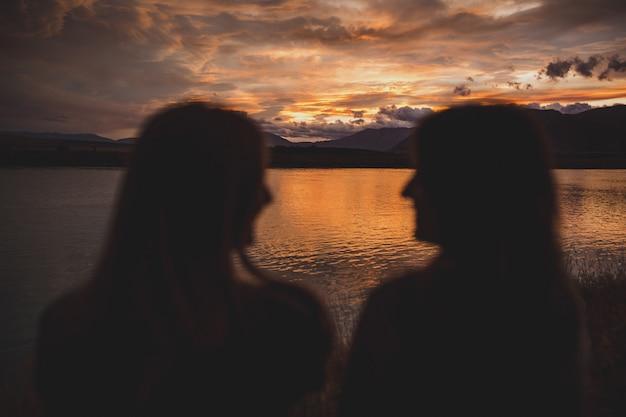 Dziewczyny Siedzą Na Brzegu Podczas Zachodu Słońca Nad Jeziorem Polka W Nowej Zelandii Darmowe Zdjęcia