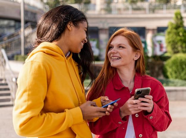 Dziewczyny Sprawdzające Telefony Na Zewnątrz Darmowe Zdjęcia