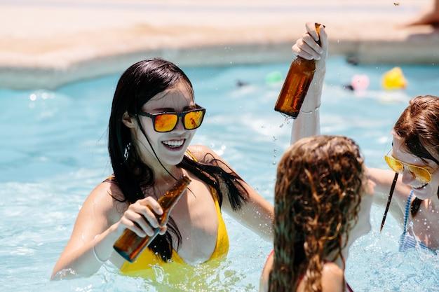 Dziewczyny Tańczą W Basenie Z Butelkami Piwa Premium Zdjęcia