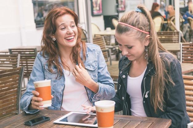 Dziewczyny Używa Cyfrowej Pastylkę Przy Kawiarnią Premium Zdjęcia