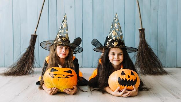 Dziewczyny w kostiumach czarownic leżących z dyni Darmowe Zdjęcia