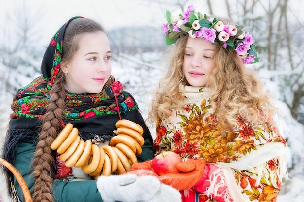 Dziewczyny w rosyjskich strojach ludowych w zimowym krajobrazie Premium Zdjęcia