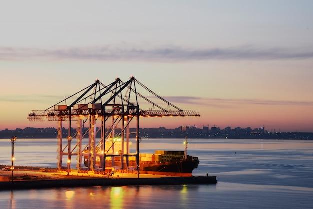 Dźwigi portowe w nocnym porcie morskim. dostawa towarów drogą morską. Premium Zdjęcia