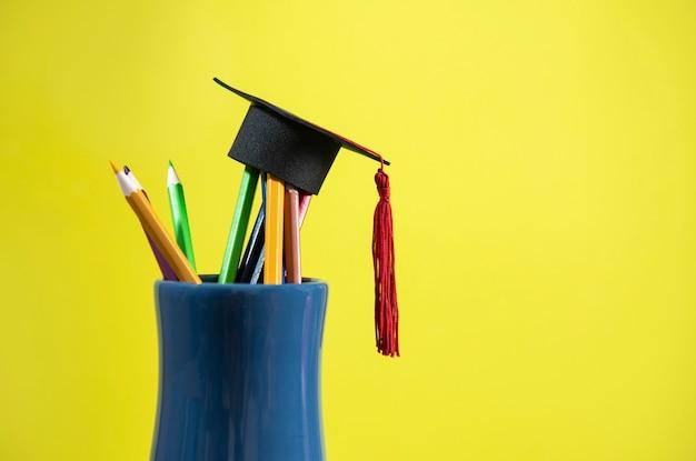 Edukacja i powrót do koncepcji szkoły z czapeczką na kolorowym ołówku w piórniku Premium Zdjęcia