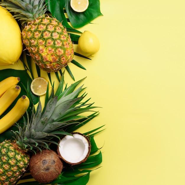 Egzotyczne ananasy, kokosy, banan, melon, cytryna, palma i monstera pozostawia na żółtym, fioletowym tle Premium Zdjęcia