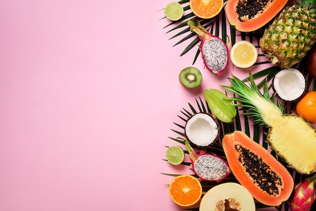 Egzotyczne owoce i liście palm tropikalnych - papaja, mango, ananas, banan, karambola, smok owoc, kiwi, cytryna, pomarańcza, melon, kokos, wapno. Premium Zdjęcia