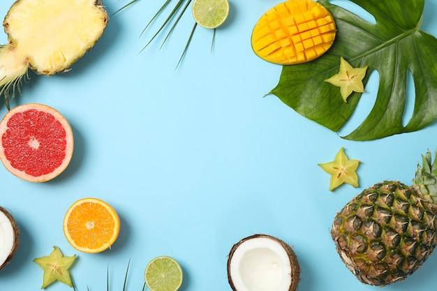 Egzotyczne Owoce I Liście Palmowe Na Niebieskim Tle, Miejsca Na Tekst Premium Zdjęcia