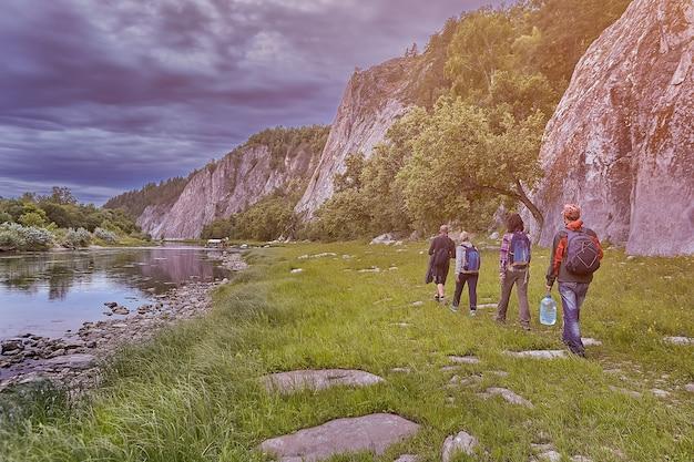 Eko-turystyka, Wędrowcy Grupowi Spacerujący ścieżką Wzdłuż Rzeki, W Dzikim, Skalistym Terenie. Premium Zdjęcia