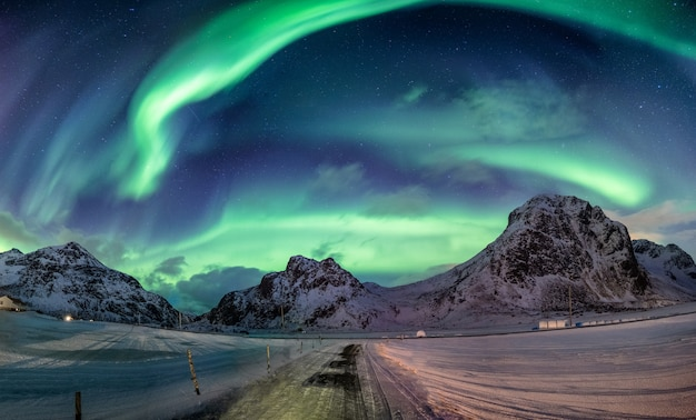 Eksplozja zorzy polarnej w śnieżnym paśmie górskim Premium Zdjęcia