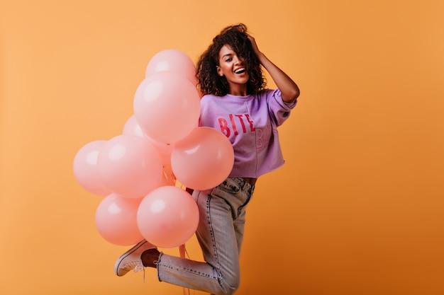 Ekstatyczna Modelka W Dżinsach Tańczy Na Przyjęciu Urodzinowym. Afrykańska Dziewczyna Debonair Hoding Kilka Balonów Z Helem. Darmowe Zdjęcia