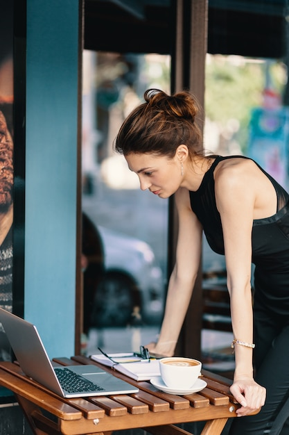 Elegancka Biznesowa Kobieta Stoi Blisko Stołu W Kawiarni Podczas Gdy Patrzejący Laptop Darmowe Zdjęcia